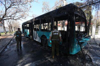Un bus quemado tras incidentes y enfrentamientos en la comuna de Huechuraba