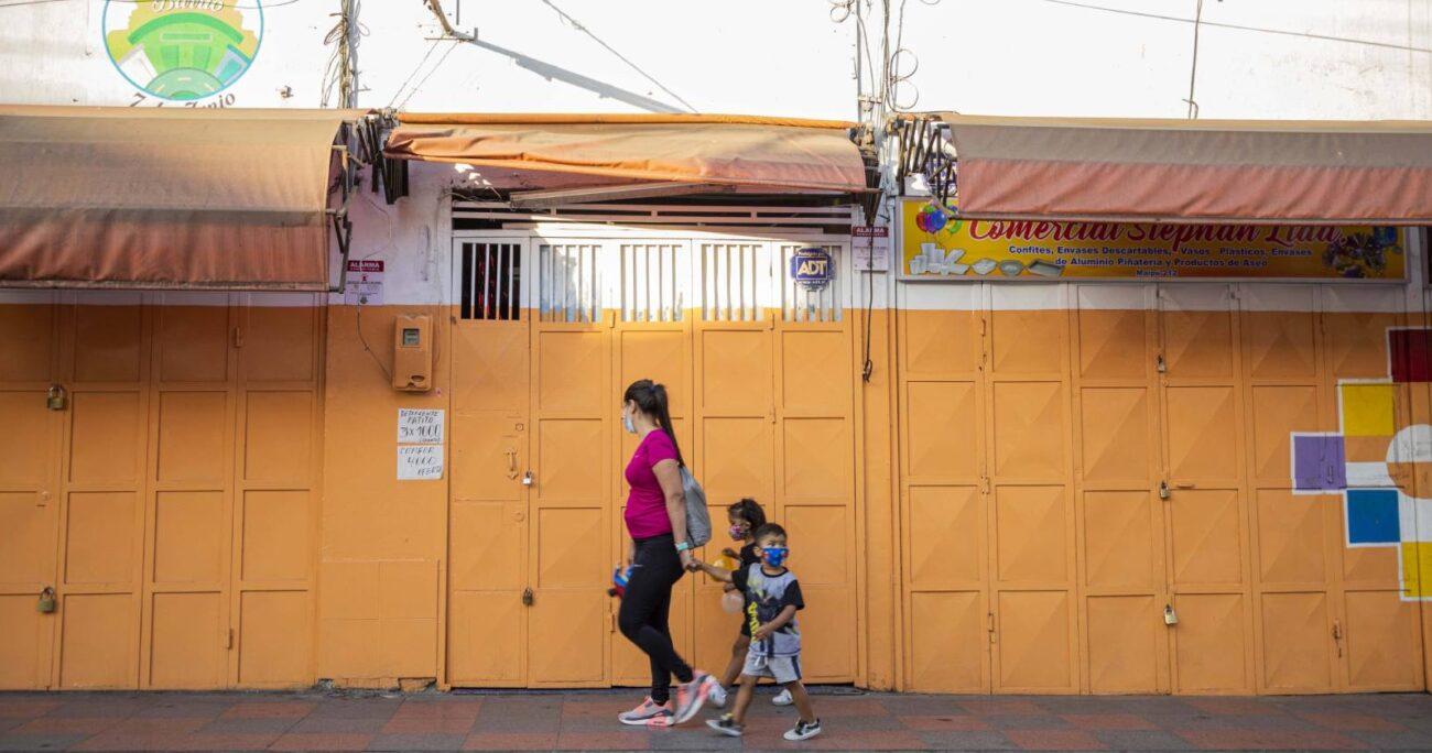 Mujer junto a sus hijos transita por locales comerciales cerrados debido a la cuarentena en Arica. (Agencia UNO/Archivo)