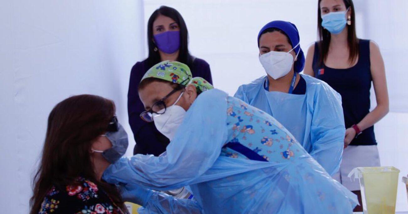La ministra Karla Rubilar y la seremi Paula Labra durante el inicio de la vacunación. (Min. Desarrollo Social)