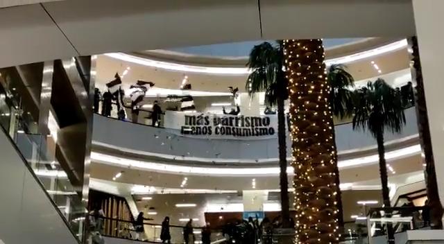 """Llegaron hasta el centro comercial con lienzos para protestar bajo la consigna """"más barrismo, menos consumismo""""."""