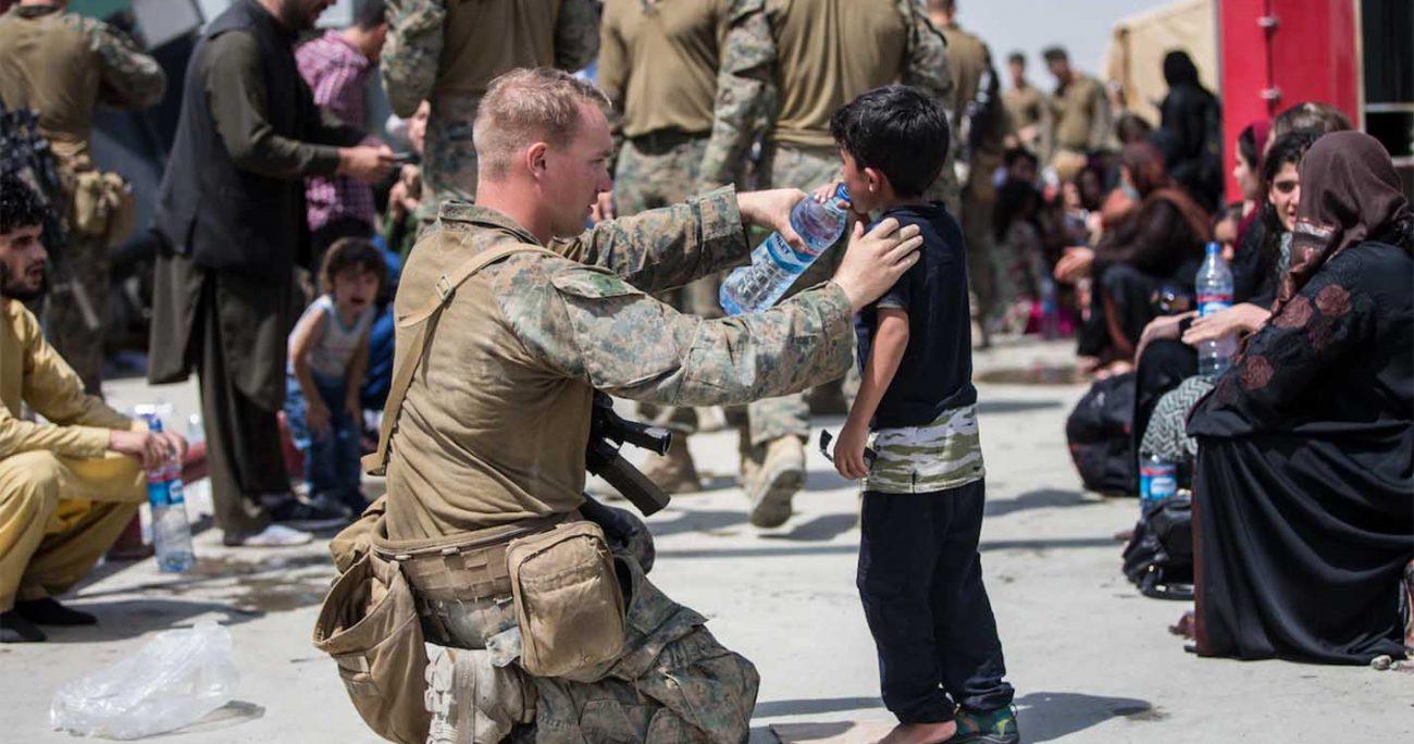 Soldados norteamericanos asisten a niños afganos en el aeropuerto de Kabul, quienes están a la espera para abandonar su pais tras la ola de violencia que llegó con los talibanes.  DOD